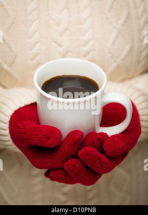 Donna in felpa con Rosso stagionale muffole tenendo una tazza di caffè caldo. Foto Stock