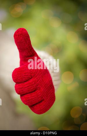 Donna in felpa con Rosso stagionale muffole tenendo fuori un pollice in alto segno con la mano. Foto Stock