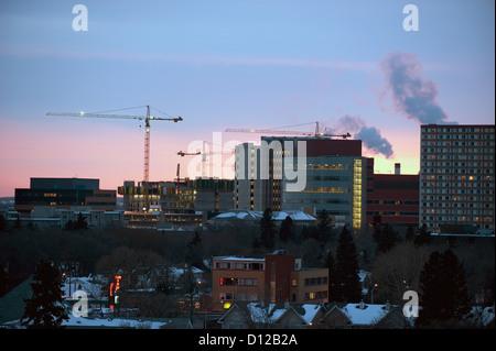 Gli edifici e le gru della skyline al tramonto; Edmonton Alberta Canada Foto Stock