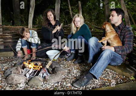Famiglia rilassante dal fuoco all'aperto Foto Stock