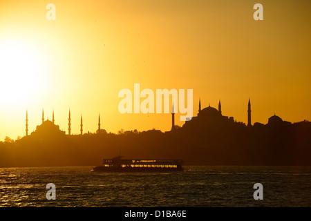 La moschea blu e Hagia Sophia minareti sagome al tramonto sul Bosforo con barca retroilluminato Istanbul TURCHIA Foto Stock