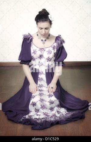 Una donna in un periodo il vestito è seduta sul pavimento Foto Stock