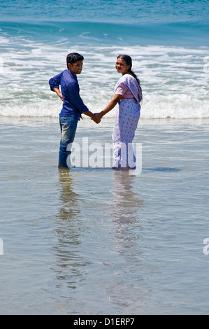 Ritratto verticale di una coppia felice coppia indiana in piedi sul mare completamente vestito tenendo le mani sulla Foto Stock