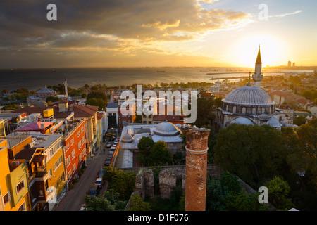 Sole che tramonta dietro la Sokollu Mehmet Pascià minareto della moschea con bagliore dorato sulle case e il Mare Foto Stock