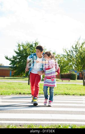 Ragazzo e una ragazza attraversando via a crosswalk su un corso chiuso Foto Stock