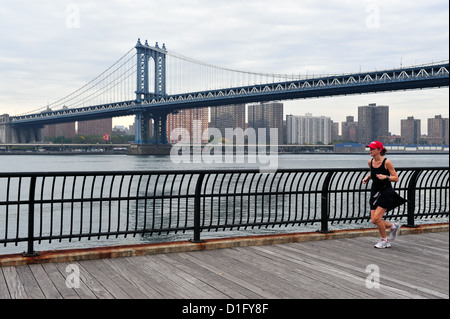 Donna americana corre sotto Manhattan Bridge su 10 Ottobre 2009 in Manhattan New York. Foto Stock