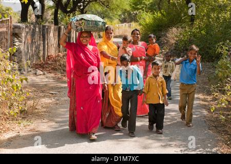 Un felice sorridente colorata famiglia indiana gruppo di donne ragazzi ragazze e un bambino di ritorno da shopping su una strada tranquilla in India Asia