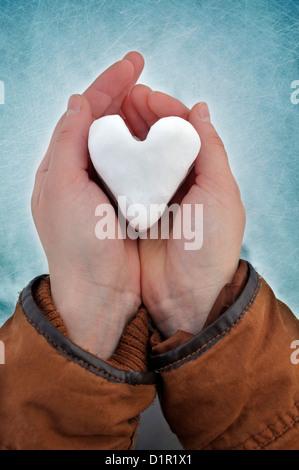 Giovane donna di contenimento a forma di cuore snowball Foto Stock