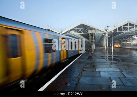 Avvicinando il treno in caso di nebbia e la nebbia a Southport Stazione ferroviaria_ Northern Line rete Merseyrail Merseyside, Regno Unito Foto Stock