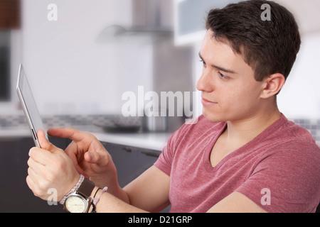 Giovane uomo utilizzando una tavoletta digitale, guardando lo schermo o monitor. Situato in una cucina moderna. Foto Stock