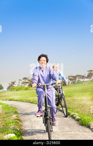 Seniors asiatica giovane mountain bike nel parco Foto Stock