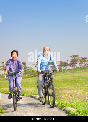 Felice seniors asiatica giovane mountain bike nel parco Foto Stock