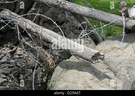 La rottura di un filo spinato con staccionata in legno posti in un campo in Cotacachi, Ecuador Foto Stock