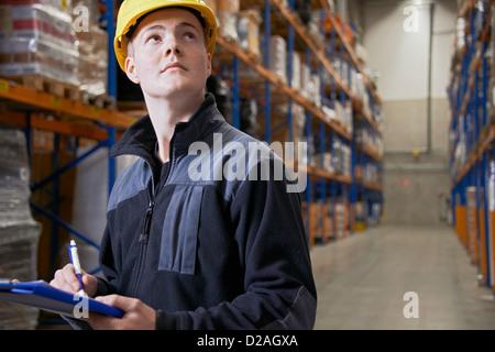 Lavoratore controllare le scorte in magazzino Foto Stock