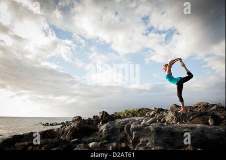 La donna a praticare yoga sulla formazione di roccia Foto Stock