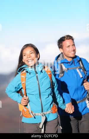 Giovane sportivo felice interracial escursionismo coppia tenendo le mani sulla montagna escursione a piedi al di fuori in alta montagna Foto Stock