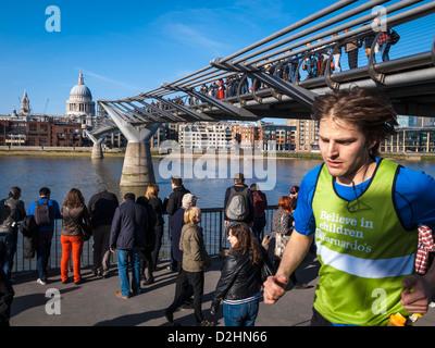 Un giovane uomo che corre sotto il Millenium Bridge in una giornata di sole Foto Stock