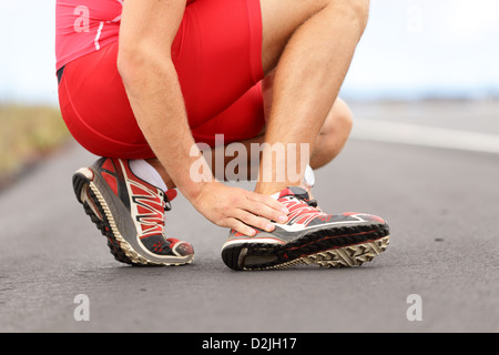 Sezione bassa del giovane maschio runner toccando il piede nel dolore a causa della caviglia slogata su strada Foto Stock