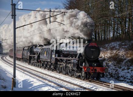 I treni, le vie e i passeggeri LMS 4-6-0 Numero 44871 Midlander treno a vapore su strade coperte di neve via d'inverno. Foto Stock