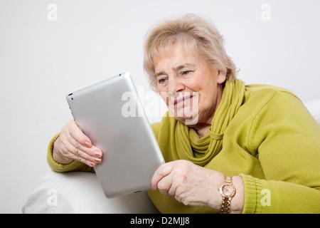 Signora matura utilizzando una tavoletta digitale. Foto Stock
