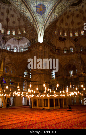 Vista interna della Moschea Blu ( Sultan Ahmet Camii ) con uomo musulmano prega sulla red tappetino, Sultanahmet Foto Stock