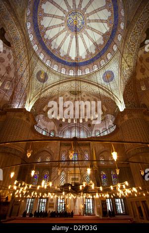 La Moschea Blu ( Sultan Ahmet Camii ): vista interna con uomini musulmani pregare attraverso le finestre di vetro Foto Stock