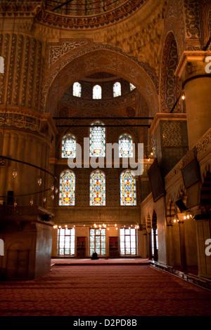 La Moschea Blu ( Sultan Ahmet Camii ): vista interna con uomo musulmano di pregare con il vetro di finestra - Sultanahmet Foto Stock
