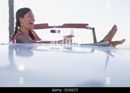 Ragazza ridere tramite telefono cellulare nel convertibile Foto Stock