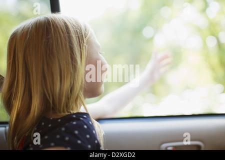 Ragazza di raggiungere al di fuori della finestra di auto Foto Stock