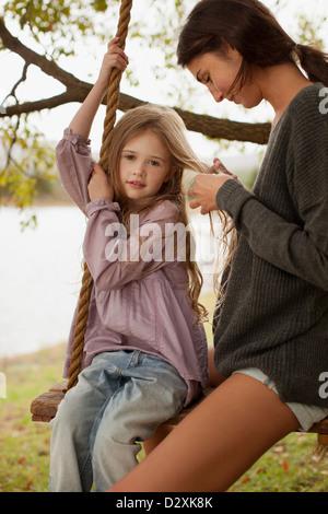 Calza di madre figlia di capelli su swing sul lago Foto Stock