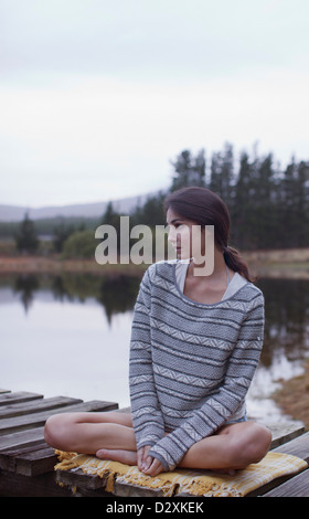 Malinconici donna seduta sul dock a lago Foto Stock