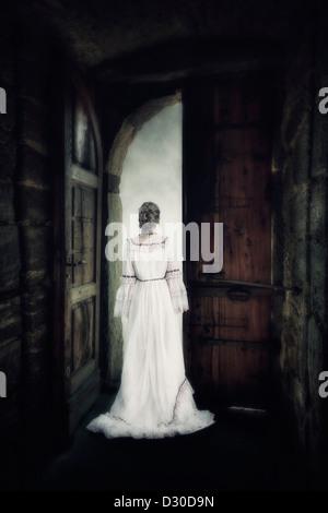 Una donna in un elegante abito è in piedi al gate di un vecchio castello