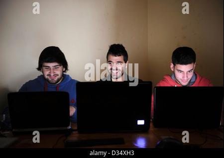 Tre giovani uomini utilizzando computer portatili Foto Stock
