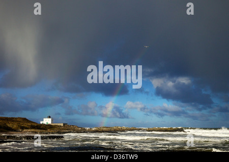 Rainbow e navigare su rocce Harkness, Bamburgh Lighthouse, Northumberland, North East England, Regno Unito, GB,