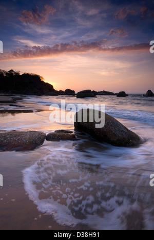 Il lavaggio delle onde sulle rocce sulla spiaggia Foto Stock