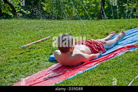 8 anno vecchio ragazzo caucasico sta avendo divertimento estivo facendo scorrere indietro verso il basso da un foglio Foto Stock