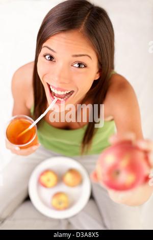 Ritratto di felice eccitato giovane razza mista donna mostra Apple mentre si beve succo di mela Foto Stock
