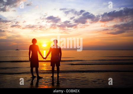 Coppia giovane in amore al tramonto in riva al mare