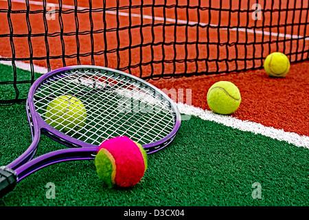 La sfera e la racchetta da tennis disposti attorno al netto su un campo sintetico. Foto Stock