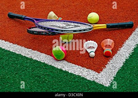 Badminton volani colorati con le palle da tennis e racchette, posto in un angolo di un campo sintetico. Foto Stock