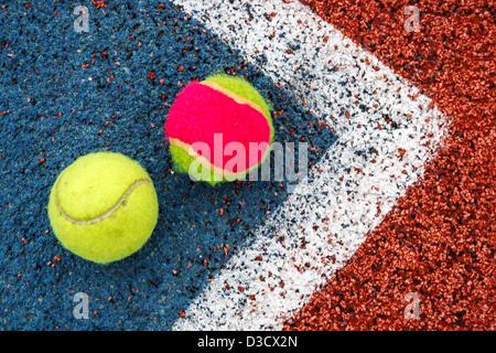 Tennis palline colorate, posto in un angolo di un campo sintetico. Foto Stock