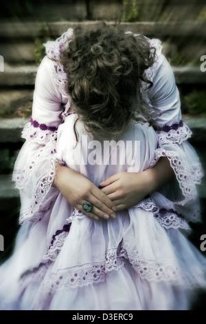 Una ragazza in un abito da sposa è seduta sul vecchio di gradini di pietra Foto Stock