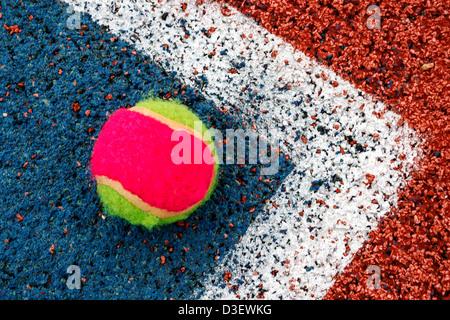 Tennis palla colorata posto in un angolo di un campo sintetico. Foto Stock