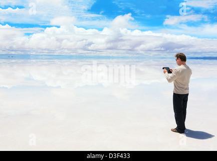 Uomo al lavoro su una tavoletta digitale nel mezzo del lago Salar de Uyuni Foto Stock