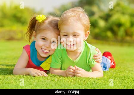 Immagine di due bambini felici divertendosi nel parco, fratello e sorella sdraiato sul verde erba, migliori amici Foto Stock
