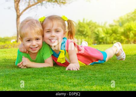 Foto di carino bambina con pretty boy sdraiati sull'erba verde nel parco, allegro bambini in appoggio sul campo Foto Stock