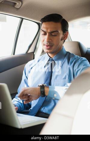 Imprenditore Bengali usando un computer portatile in un auto e controllando il tempo Foto Stock