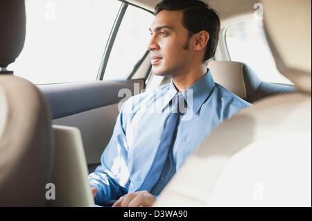 Imprenditore Bengali usando un computer portatile in un'auto Foto Stock