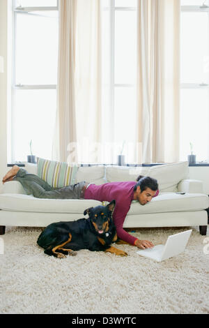 Un giovane casual uomo Hispanic-Latino divertente il suo cane da navigare in internet utilizzando il computer portatile Foto Stock