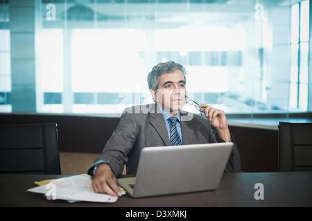 Imprenditore seduti nella parte anteriore del computer portatile perso in pensieri Foto Stock